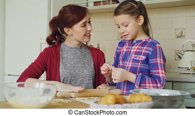 Cheerful mother cooking in the kitchen while cute daughter coming and embracing mom in the morning. Family, food, home and people concept