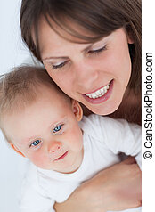 Cheerful mother holding her cute baby