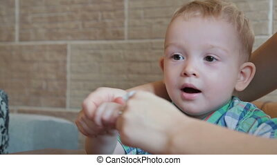 Cheerful mother is teaching her son to talk and wipe his hand