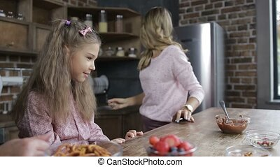 Cheerful mother offering daughter homemade cookies
