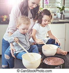 Cheerful mother teaching her children how to bake a cake