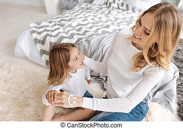 Cheerful mother touching the hands of her daughter