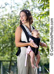 Cheerful mother with baby in sling