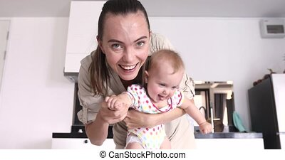 Cheerful mother with funny baby in kitchen - Mother waves...