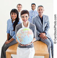 Cheerful multi-ethnic business people holding a terrestrial globe in the office