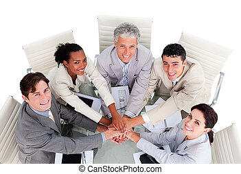 Cheerful multi-ethnic business team with hands together in a meeting