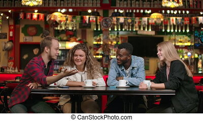 Cheerful multi-ethnic company of friends in a restaurant...