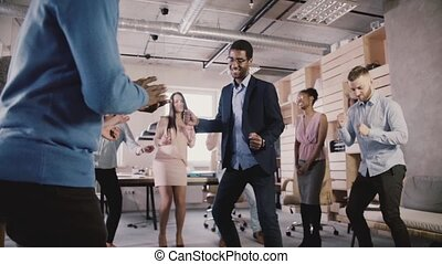 Cheerful multiethnic business people dance together at healthy office teambuilding party, celebrate success slow motion.