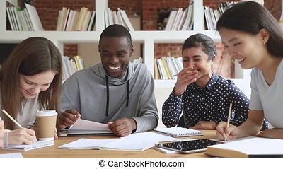 Cheerful multiethnic students team laugh at funny joke study...