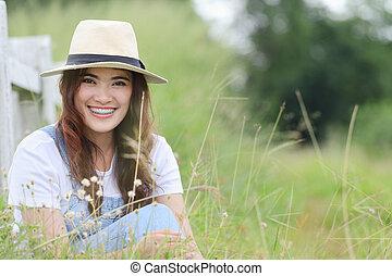 Asian woman - Cheerful multiracial Asian woman wearing a hat...