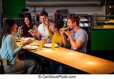 Cheerful multiracial friends having fun eating pizza in...