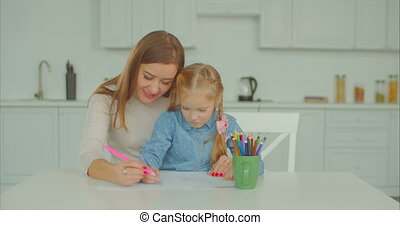 Cheerful mum and child busy with drawing at home - Positive...