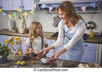 Cheerful mum and kid painting chicken eggs for holiday