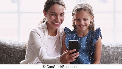 Cheerful mum showing cute small daughter funny video on smartphone