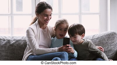 Cheerful mum showing funny mobile app having fun with kids