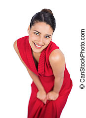 Cheerful mysterious brunette in red dress posing