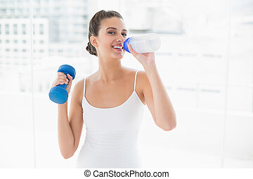 Cheerful natural brown haired woman in white sportswear drinking water while lifting a dumbbell in bright living room