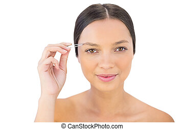 Cheerful natural woman using tweezers for her eyebrow against white background