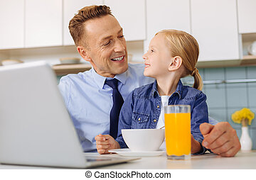 Cheerful nice man looking at his child