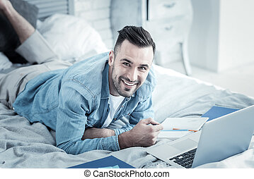 Cheerful nice man studying from home