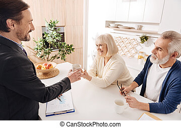 Cheerful notary having meeting with senior couple of clients