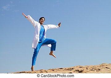 cheerful nurse jumping on beach in scrubs