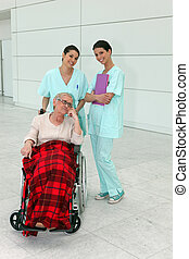 Cheerful nurses with senior woman in wheelchair