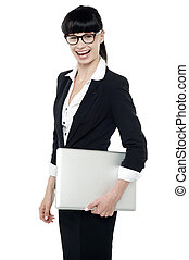 Cheerful office employee holding laptop
