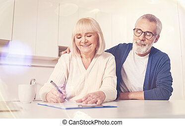 Cheerful old couple signing insurance contract