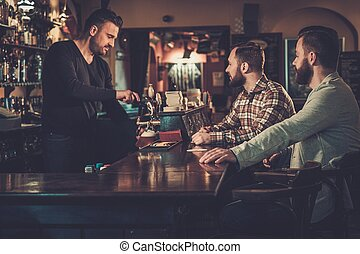 Cheerful old friends drinking draft beer at bar counter in...