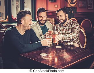 Cheerful old friends having fun and drinking draft beer in ...