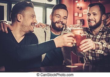 Cheerful old friends having fun and drinking draft beer in...