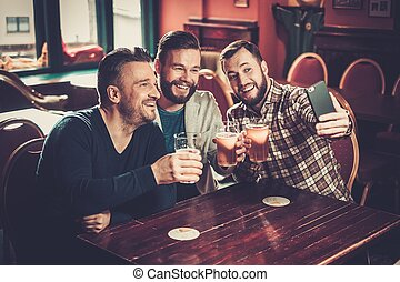 Cheerful old friends having fun taking selfie and drinking draft beer in pub.