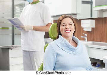 Cheerful old lady is visiting dental doctor
