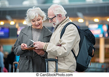 Cheerful old man and woman are waiting for their journey