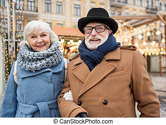 Cheerful old man and woman relaxing in city