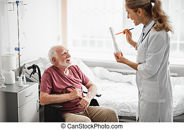 Cheerful old man in wheelchair listening doctor