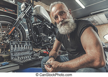 Cheerful old man ready for motorbike renovation - Sincere...