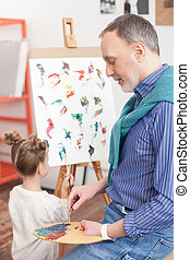 Cheerful old painter and his small grandchild - Pretty...