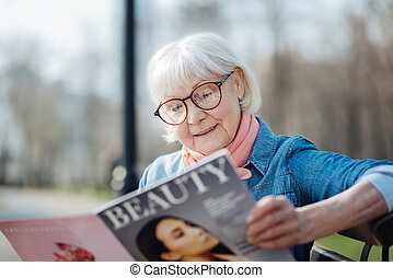 Cheerful old woman reading a magazine