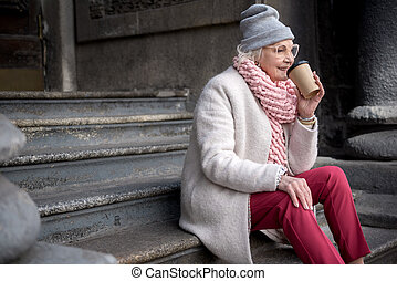Cheerful old woman relaxing outside with hot espresso
