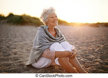 Cheerful old woman sitting on the beach - Happy retired ...