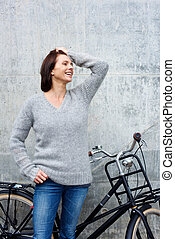 Cheerful older woman standing with bike