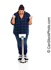 successful weight loss - cheerful overweight girl on scale...