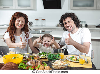 Cheerful parents and child showing ok sign while eating