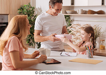 Cheerful parents congratulating daughter with holiday at home