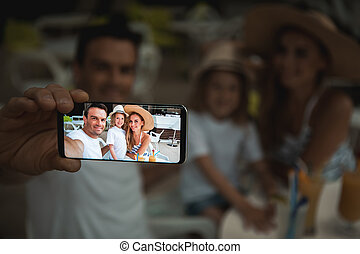 Cheerful parents photographing with child on mobile