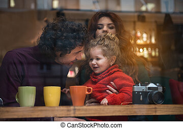 Cheerful parents spending time with their child indoors