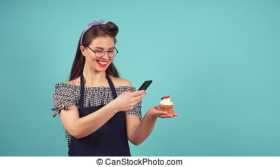 Cheerful pastry girl makes photo of her cupcake. - Cheerful...