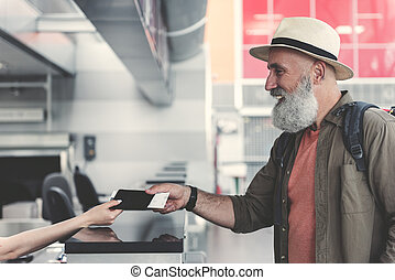 Cheerful pensioner giving ticket in booking office - Side...